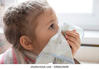 Sick girl sneezing In handkerchief