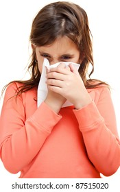 Sick girl sneezing on a paper tissue isolated on white