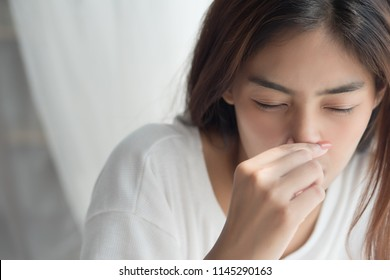 sick girl sniffle with runny nose; sick woman suffering from cold, flu, runny nose, trying to clear her nose; woman personal health care, pain, sickness concept; asian young adult woman model