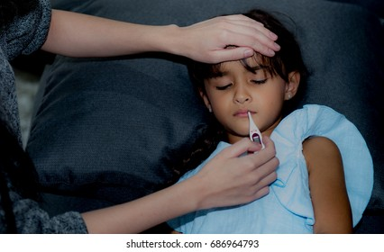 Sick girl with thermometer laying on sofa and mother hand taking temperature, Mother checking temperature of her sick girl who has thermometer in his mouth, Sick child with fever and illness, Age 7