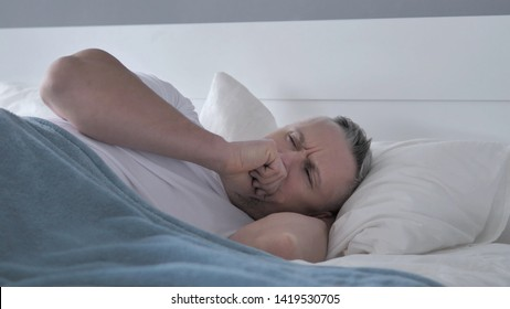 Sick Gray Hair Man Coughing while Sleeping in Bed