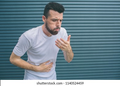 Sick guy is vomiting. He is trying to prevent it. He holds one hand on stomack and another one close to mouth. Isolated on striped and blue background.