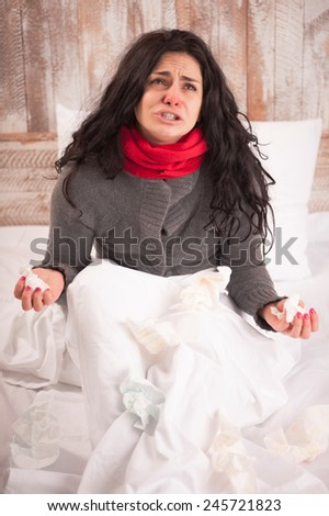 Sick and hopeless. Young woman with flu wearing thick scarf raising her hands with tissues in despair while sitting in bed on country house background