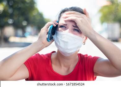 Kranke Mädchen ängstliche Frau in Maske leiden an Hitze, Kopfschmerzen Anruf Krankenwagen, sprechen auf Handy, fühlen sich schlecht. Person braucht Hilfe. Virus, Chinesisches pandemisches Koronavirus, Panikkonzept.