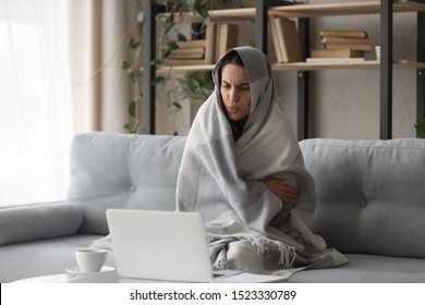 Sick ill young woman feel cold covered with blanket sit on sofa watching movie on laptop, annoyed girl shiver freezing warming at home wrapped with plaid, no central heating problem and flu concept