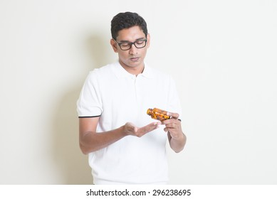Sick Indian guy taking tablet medicine. Asian man standing on plain background with shadow and copy space.