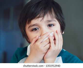 Sick kid blowing nose into tissue, Unhealthy child suffering from running nose or sneezing and covering his nose and mouth, A boy catches a cold when season change, childhood wiping nose with tissue