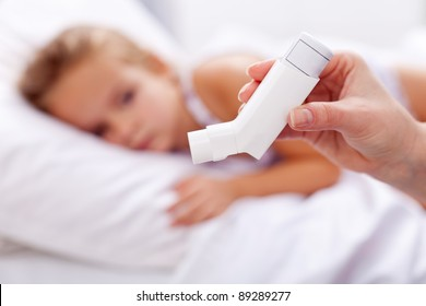 Sick kid with inhaler in foreground - asthma or other respiratory illness