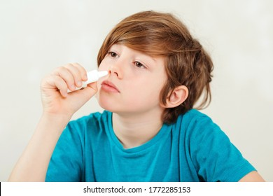 Sick kid with runny nose using nasal medicine spray. Nasal allergy. Kid with ill disease treatment season. Allergic kid, flu season. Boy has a virus, runny nose and headache. Schoolboy with runny nose