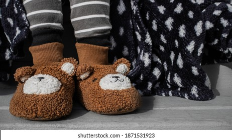 Sick kid wearing fuzzy slippers with a blanket