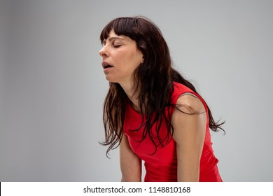 Sick lethargic woman in pain hunching her shoulders and groaning with closed eyes over grey