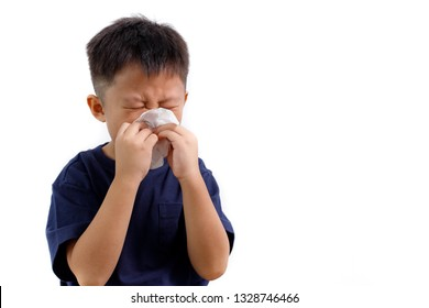 Sick little Asian boy using paper tissues while sneezing. Respiratory disease.