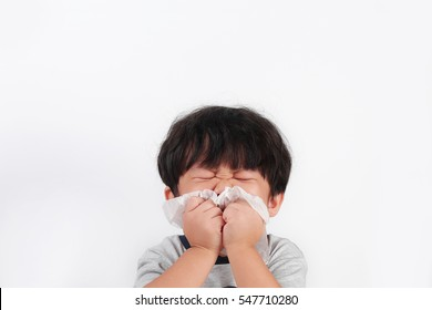 Sick little Asian boy wiping or cleaning nose with tissue isolated white background