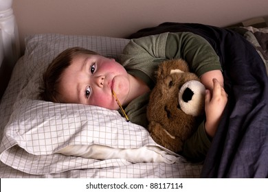 sick little boy with bright red cheeks and thermometer in mouth, hugs his teddy bear in bed