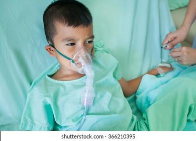 sick little boy makes inhalation in hospital room.