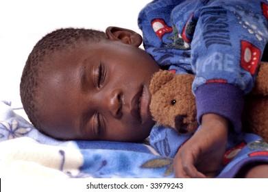 Sick little boy sleeping with his teddy bear