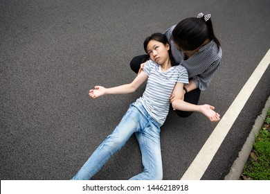 Sick little child girl with epileptic seizures outdoor,daughter suffering from illness with epilepsy during seizure attack,asian young woman or mother care of girl patient,brain,nervous system concept