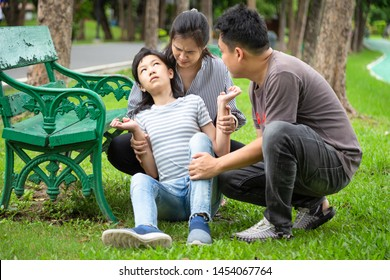 Sick little child girl with epileptic seizures in outdoor park,daughter suffering from seizures,illness with epilepsy during seizure,asian mother,father care of girl patient,brain,family care concept