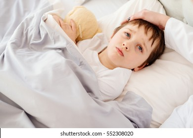Sick little child with temperature in bed. Hand of doctor on his forehead