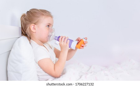 Sick little girl with asthma medicine lying in bed. Unwell kid with chamber inhaler for cough treatment. Flu season. Bedroom or hospital room for young patient. Healthcare and medication.