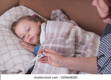 Sick little girl in bed. Mother with thermometer is sitting near the bed.