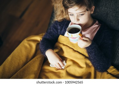 Sick little girl blowing her nose drinking tea
