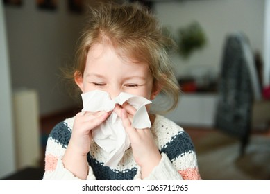 Sick little girl blowing her nose and covering it with handkerchief with eyes closed