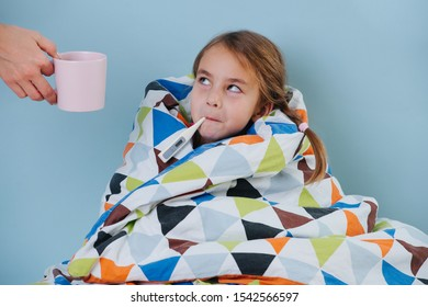 Sick little girl with a common cold is sitting in bed under blanket with electric thermometer in her mouth. Mother's handing warm herbal tea. Girl is wrapped in a blanket, so only her head is seen.