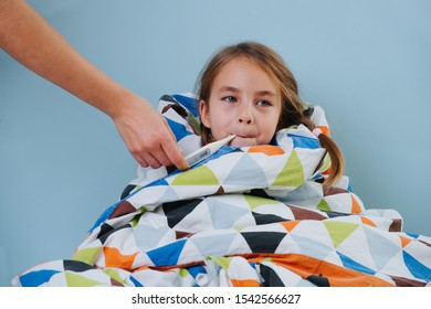 Sick little girl with a common cold is sitting in bed under blanket with electric thermometer in her mouth. Mother's hand reaching for it. Girl is wrapped in a blanket, so only her head is seen.