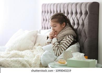 Sick little girl with cough suffering from cold in bed