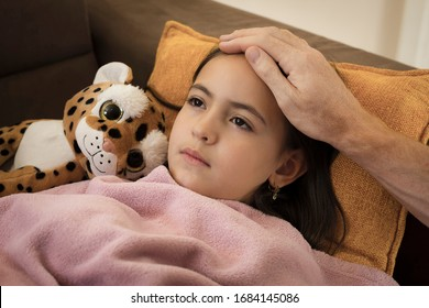 Sick little girl covered in blanket is lying on couch while her father is touching her forehead
