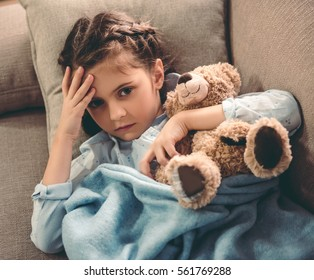Sick little girl covered in blanket is hugging teddy bear and touching her forehead while lying on couch