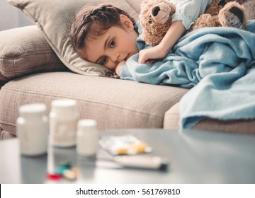 Sick little girl covered in blanket is hugging teddy bear and looking sadly on medicine while lying on couch