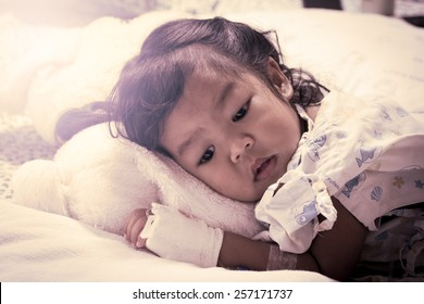 Sick little girl lay down on bed in the hospital