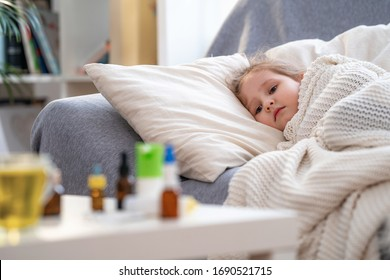 Sick little girl is lying on sofa, wrapped in a blanket. on the table are medicines. An unhealthy sad child is being treated for a viral disease, a cough medicine. epidemic of coronavirus, kovid-19.