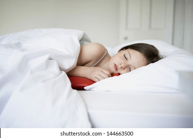 Sick little girl sleeping with hot water bottle in bed