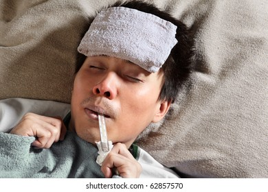 A sick male sleeping with wet towel on his forehead to reduce high high fever