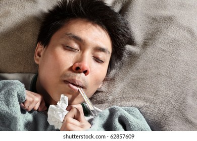 A sick male sleeping while themometer is in his mouth