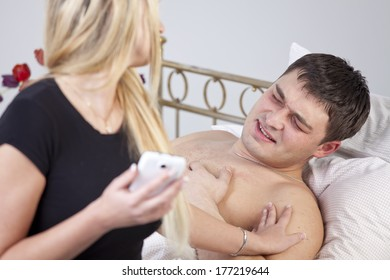Sick man with ache on bed, worried woman holding phone at his side.