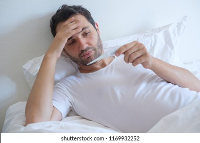 Sick man in bed measuring temperature feeling fever