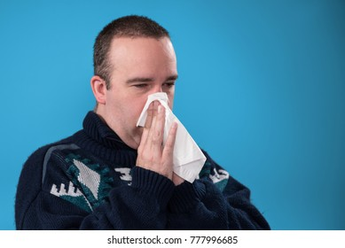 Sick man blowing his nose into a tissue