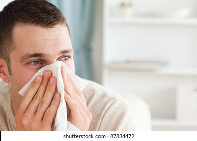 Sick man blowing his nose in his living room