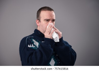 A sick man in his 30's is blowing his nose, shot against a grey background
