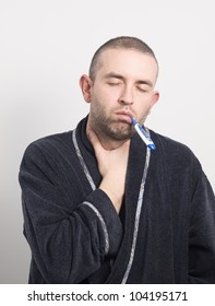 Sick man with his eyes closed. The man has a thermometer in his mouth and sore throat