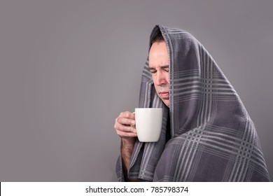 Sick man holding a hot drink and trying to stay warm.