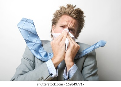 Sick man holding a tissue up to his nose sneezing with tie flying