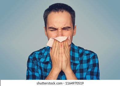 Sick man isolated has runny nose. A young guy sneezes in a pink scarf on a blue background. Colds in the fall.