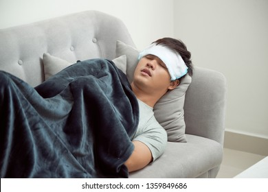 Sick man lying on sofa checking his temperature under a blanket at home in the living room