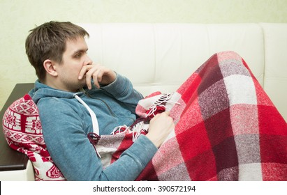 Sick man lying on sofa  at home in living room