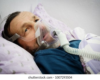 A sick man in an oxygen mask in a hospita